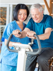 caregiver and elder man having a physical therapy