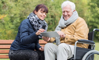 caregiver and elder man looking at the tablet